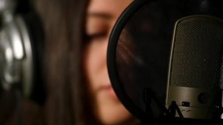 Female singer in headphones against microphone.