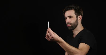 man deciding between electronic or normal cigarette on black background.