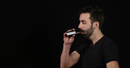 deadly: man deciding between electronic or normal cigarette on black background.