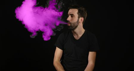 young man vaping with an electronic cigarette and make some smoke clouds. Stock Photo