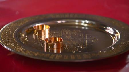 perforated: Classic gold wedding ring on a gold plate. Stock Photo