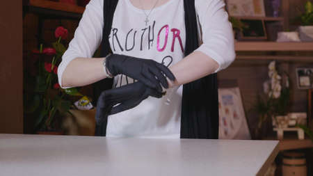 glasshouse: Beautiful florist hands girl wearing gloves. Stock Photo