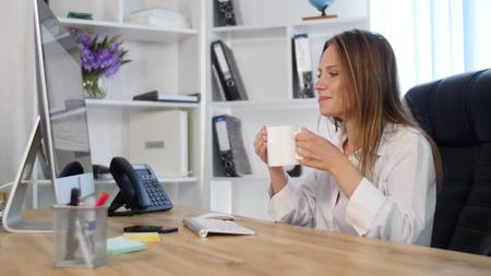 exhausting: Beautiful young woman working in office and drink coffee.