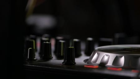 Regulators change sound settings control panel of black professional dj mixers, zoomed view. Stock Photo