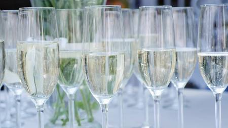 a row of glasses filled with champagne are lined up ready to be served.