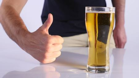 avid: Man with a glass of beer. white background. close up.
