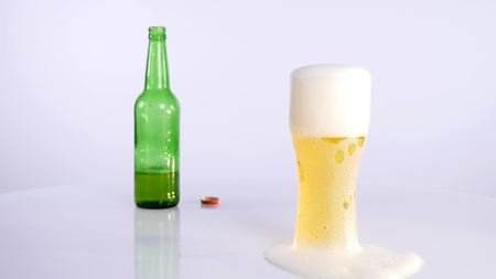drunken: A bottle of beer is poured into a cup on a white background.