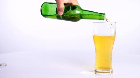 A bottle of beer is poured into a cup on a white background.