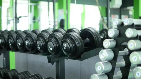 Many fitness dumbbells in the gym. Stock Photo