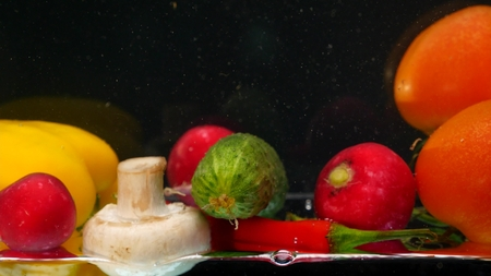 fresh vegetables falling with water on black background.
