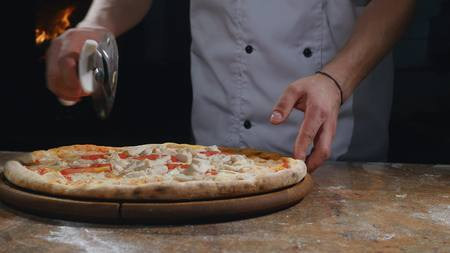woodfired: Cook in apron taking hot and hot pizza out of oven.