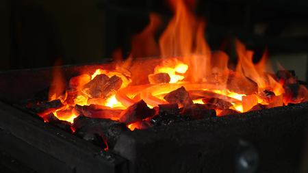 Blacksmith placed an iron hook in the fire.