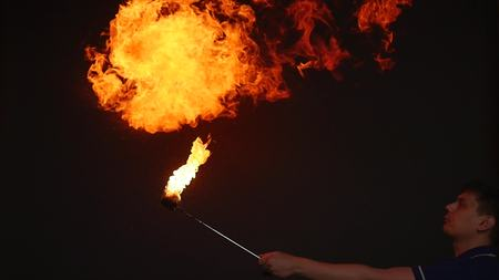Fire show performance. A man picks gasoline at a torch