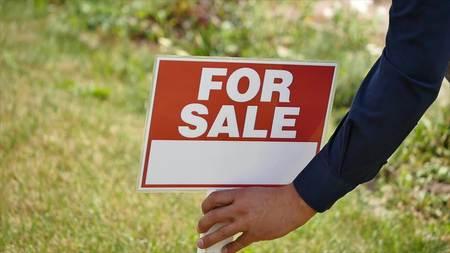 real estate sold: male hands hammer sign for sale.