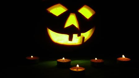Carved Halloween pumpkin lights inside with flame on a black background with lighted candles close up.