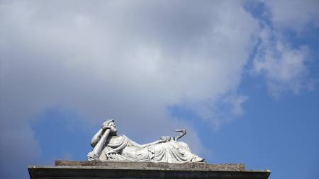 Statue in a cemetery with clouds. time lipse. Stock Photo