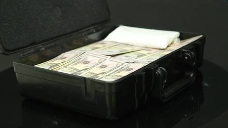 A man opens a black metal suitcase with money.