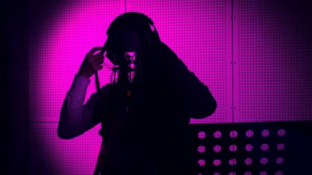 A young woman sings a song in a microphone in a recording studio under Neon light. Stock Photo