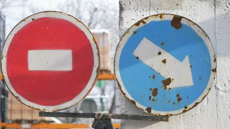 Pointing Arrow And Stop Signs Showing The Way To Drivers On The Street Stock Photo