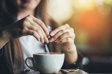 Female hand pours sugar into coffee. Sunlight background.
