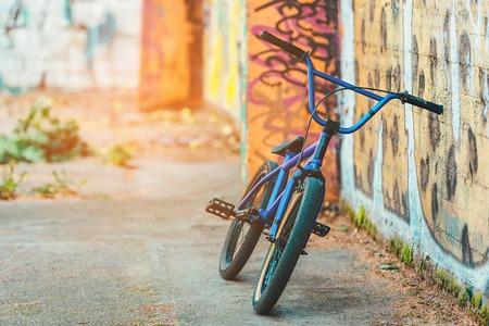 bike fix on the background wall with graffiti. sunshine background.