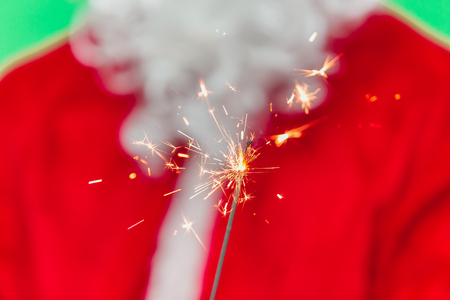 Hand of Santa Claus Hold Bengal Fire. Concept of Gifts, New Year, Eve, Santa Claus. chroma key. close up. focus on bengal fire Stock Photo