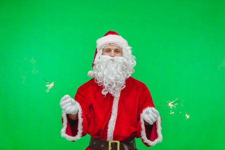 young santa claus holding winter holiday decoration - bengal fire. chroma key.