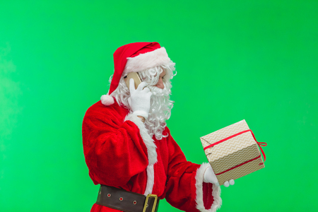 Satisfied Santa Claus speaks on the phone, laughs, sits at table with gifts, green chromakey in the background.