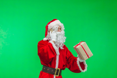 Santa Claus talking by phone and holding gift box. Christmas holiday concept. chromakey.