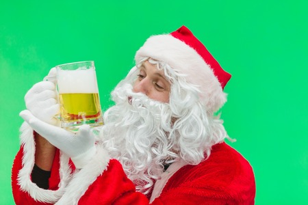 Father Christmas Santa looks at a lovely glass of beer. chroma key. close up.