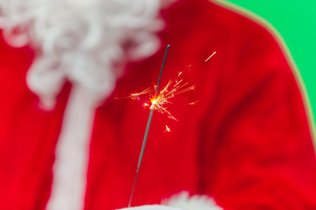 Hand of Santa Claus Hold Bengal Fire. Concept of Gifts, New Year, Eve, Santa Claus. chroma key. close up. Stock Photo