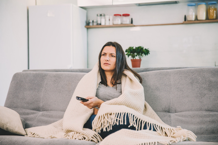 Woman looks TV on the couch