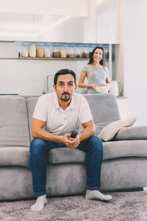 A man watches TV, while his wife looks at him