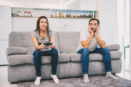 The wife plays the game while the man just sits