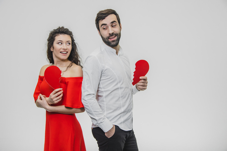 Portrait of an Excessive Couple. Conducting two parts of the heart paper. Isolated on a white background.