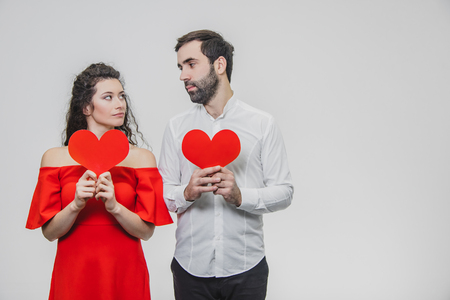 Beautiful attractive, cheerful, positive pair. Are married Hold large red cards in their sleeves. When they look at each other.