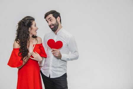 Family, holidays, Valentines Day. Love people concept - a big plan. Hold the red paper heart. White background. Dressed in a white shirt and a red dress.
