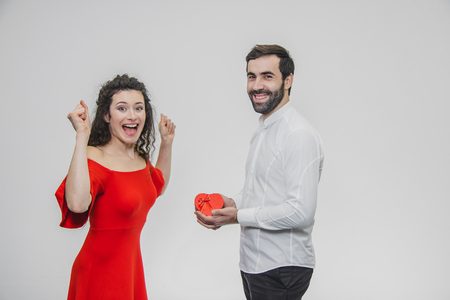 Young couple loving. A man made a present for his wife. During this time, the red field is presented in the form of a heart. Wife is pleasantly surprised. Dressed in a red dress and a white shirt.