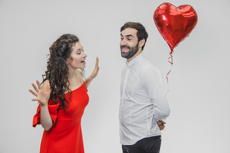 Valentine Couple. Beauty Girl and her Handsome Boyfriend holding heart shaped air balloon and kissing. Happy Joyful Family. Love.