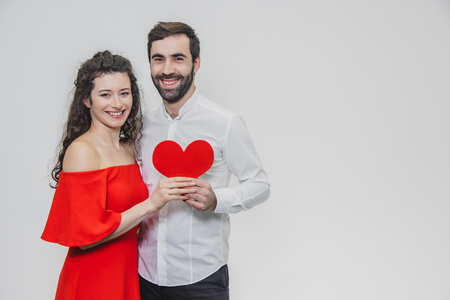 Family, holidays, Valentine's Day. Love people concept - a big plan. Hold the red paper heart. White background. Dressed in a white shirt and a red dress.