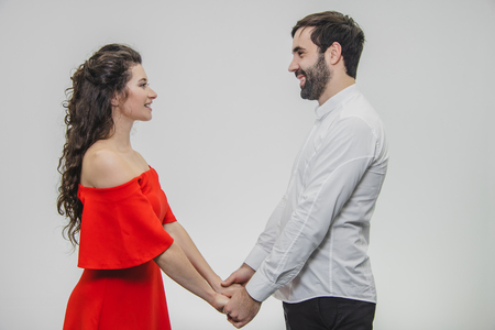Young tender and in love couple. Hold hands with each other looking straight into your eyes. Dressed in red dress and white shirt. White background.