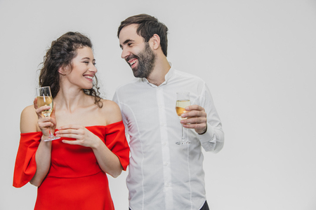 Loving young couple drinks champagne. On a white background. Dressed in red dress and white shirt. Happy together.