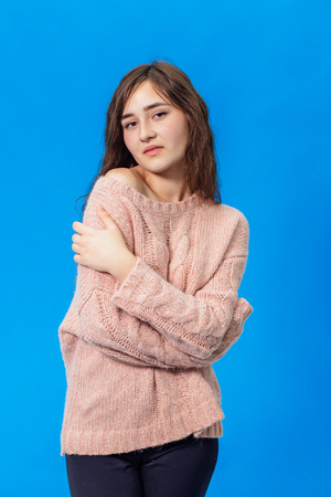 Young beautiful girl isolated on blue background