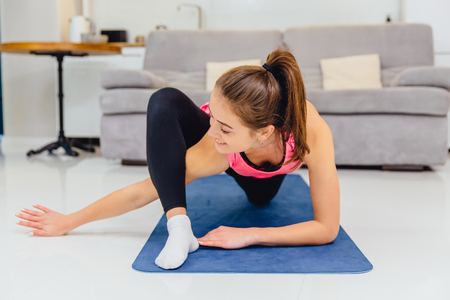 A young adult girl wearing sportswear at home, doing home fitness and training abdominal cavities in the living room.