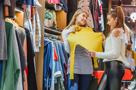 Two friends choose sweaters during shopping. Keeping the yellow and green sweaters is a hanger. Feel good, smiling and laughing. Stock Photo