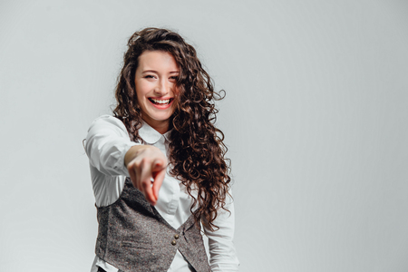 Portrait of attractive business woman on white background. With plenty of copy space. With beautiful curly hair, putting your index finger forward