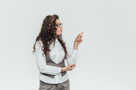Cute young business girl in suit and glasses. Surprised with one hand covers the mouth, the other at the same time raised up on a white background. Imagens