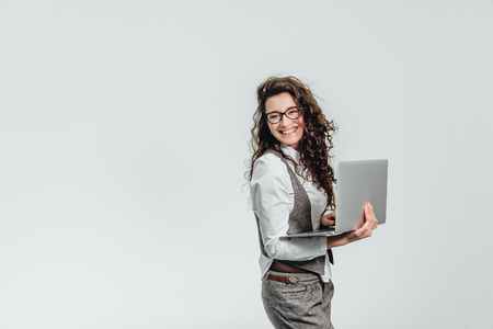 Beautiful young girl smiles. Works on a laptop in glasses and a white shirt - isolated on white