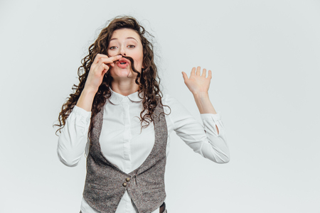 Young business lady with beautiful curly hair on a white background. During this time he puts his hair like a mustache, cope space