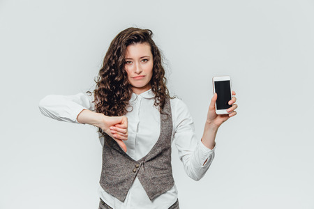 Young business lady with beautiful curly hair on a white background. During this, puts the index finger down, indicating that the phone is badly portrayed Фото со стока